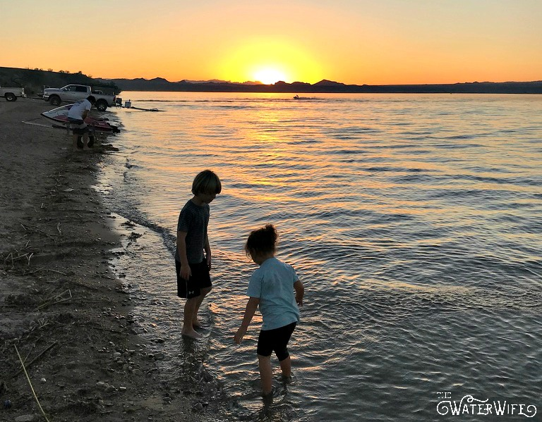 small boy and girl on the shore of the beach at sunset